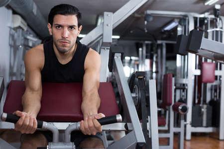 Man training on fitness machine in gym