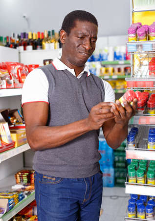 Cheerful afro man standing near rack and choosing spice in store