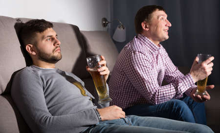 Indifferent gu with friend emotionally watching tv