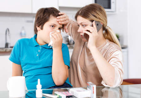Mother calling doctor, son sneezing