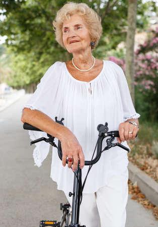 Senior woman resting near bike Фото со стока
