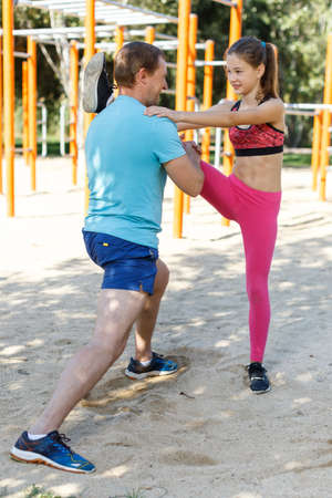 Man with daughter during workout outdoors