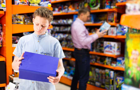 Teen boy with carton box in toy store