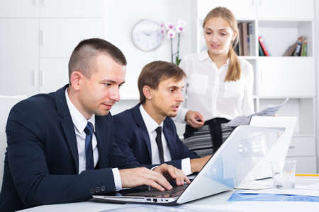 Serious active man manager working with colleagues in office