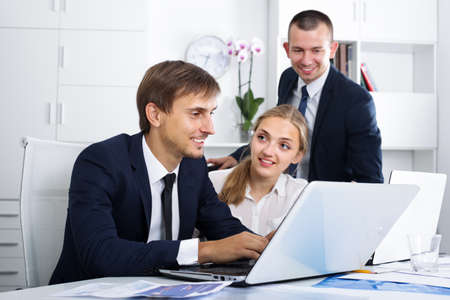 Three happy coworkers working in company office