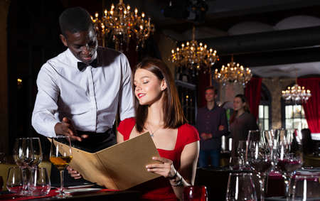 African-american waiter receiving order from guest in fashionable restaurant