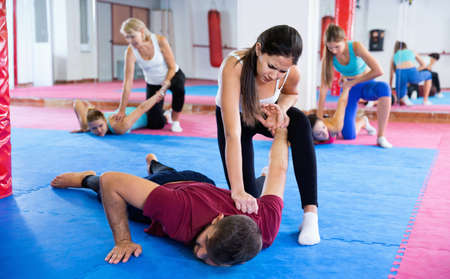Female is training self-defence moves in pair with trainer in sporty gym. Archivio Fotografico