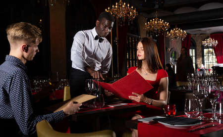 Couple with menu is giving order to african-american waiter in fashionable restaurant