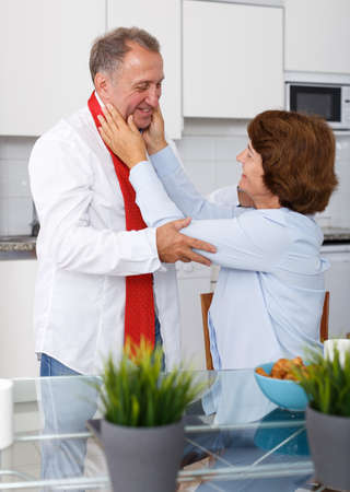 Mature woman adjusting tie to man at kitchen table at home interior