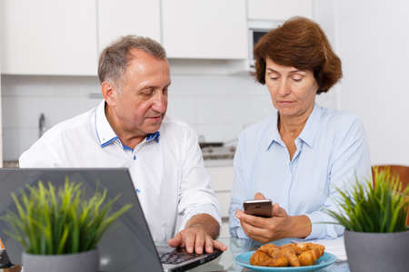 Mature man and woman using smartphone and working at laptop