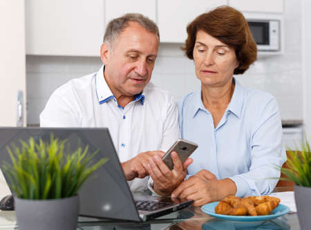 Upset mature man and woman using smartphone and working at laptop