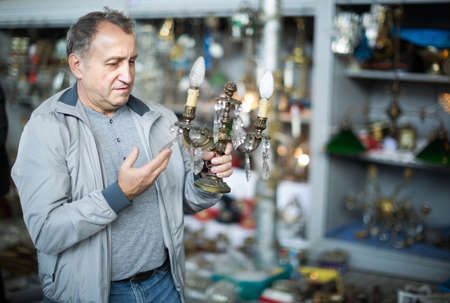 Portrait of senior male holding vintage souvenir