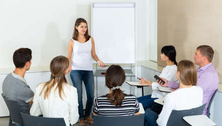 Woman reading out report to colleagues