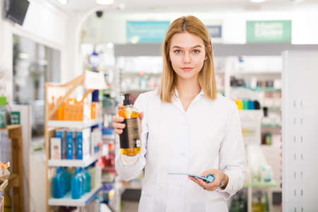 Portrait of friendly laughing pharmacist working in modern farmacy Stockfoto
