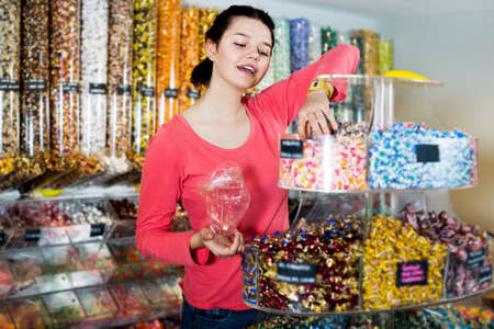 Woman posing to photographer picking different candies