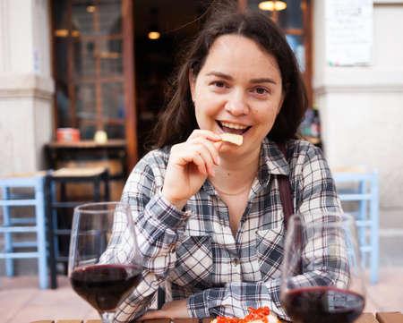 Woman enjoying wine with chips and bruschettas at outdoor restaurant Foto de archivo