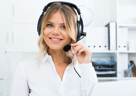 Young call center employee in headphones is sitting near laptop in the office Banco de Imagens