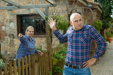 Irritated farmer with wife berating him