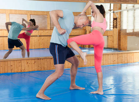 Active woman with professional trainer are training captures on the self-defense course in gym
