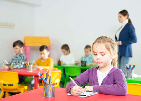 Assiduous little girl at lesson