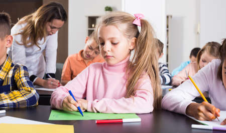 Girl and children in elementary age at drawing lesson