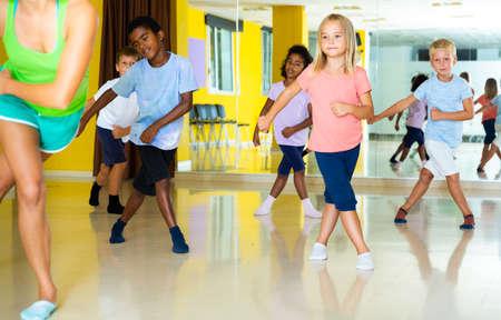 Emotional children performing modern dance in fitness studio Foto de archivo