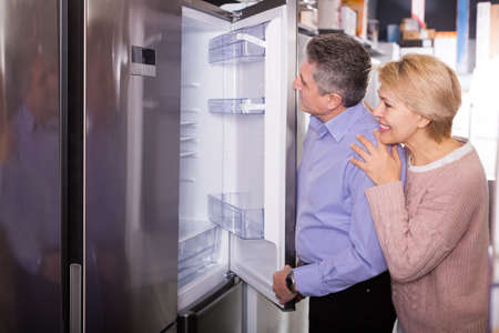 Mature married couple choose for themselves refrigerator