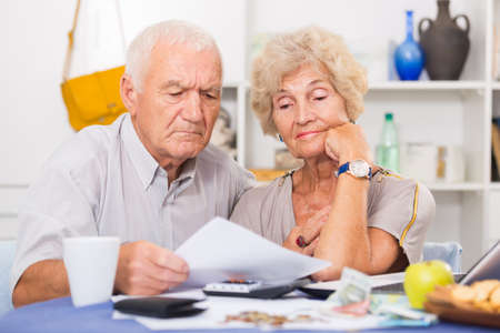Upset retired couple calculating domestic finances