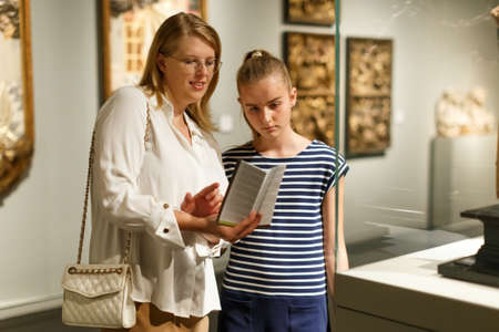 Girl with woman looking with interest at art objects in museum Imagens