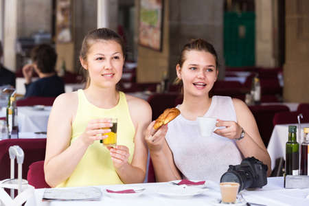 female friends traveling and drinking tea with bakery in lunch Foto de archivo