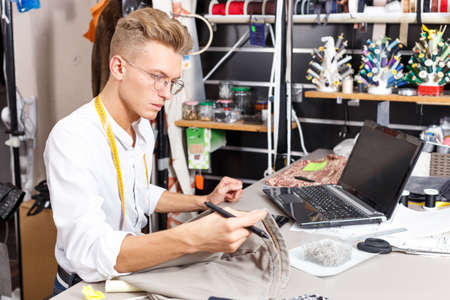 Tailor using laptop and graphics tablet