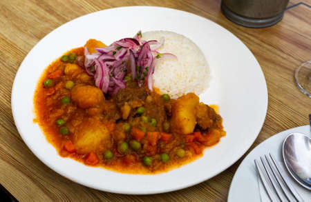 Dish of Peruvian cuisine, stewed meat with potatoes and peas