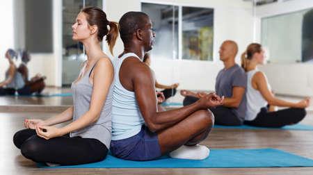 Women and men sitting back to back on mats and making padmasana pose