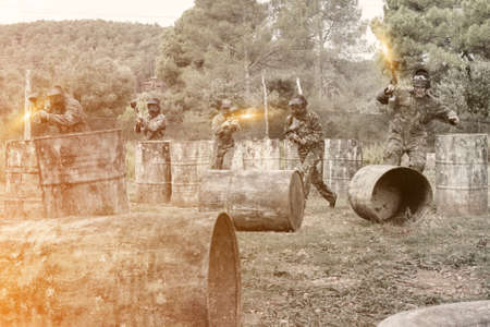 Team of adult people playing paintball on battlefield outdoor, r Stock fotó