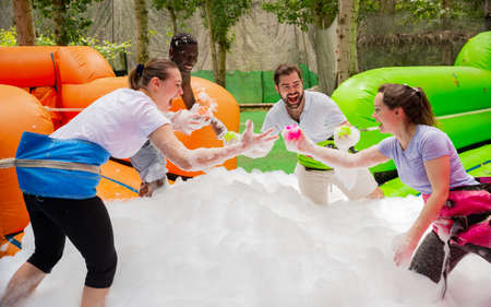 Game of funny friends in soap suds on an inflatable trampoline Imagens