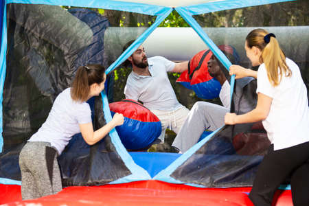 Gambling friends boxing giant gloves on an inflatable trampoline in an amusement park