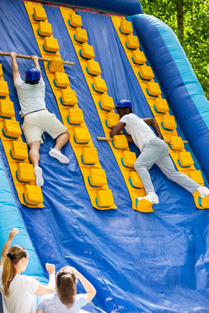 Mens competition on an inflatable slide Great race in an amusement park
