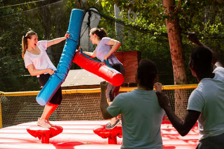 Women fighting by inflatable logs