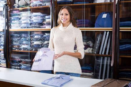 friendly female seller demonstrating shirts in men cloths store