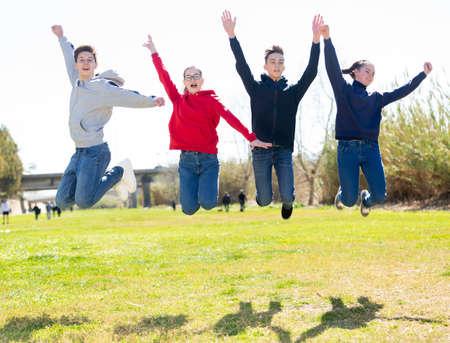 Four joyful teens jump on a lawn
