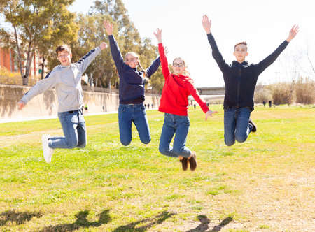 Friendly teenagers jumping together in park