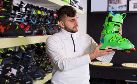 Young man choosing ski boots in store of sports equipment
