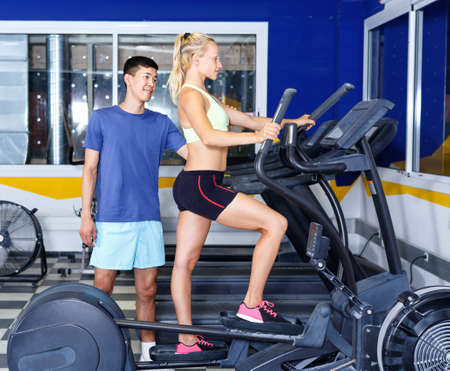 Young fitness man and woman doing cardio workout on fitness machines at gym