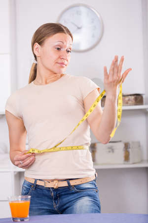 Frustrated woman measuring waist
