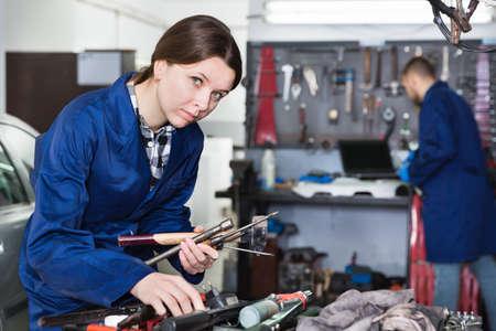Female master is choosing instruments in workshop