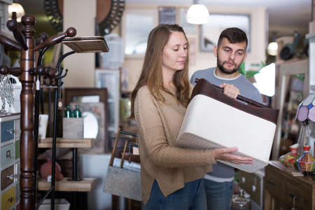 Woman looking for stylish knickknacks for apartment in shop Imagens