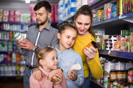 Happy family with two little girls buying food products in supermarket