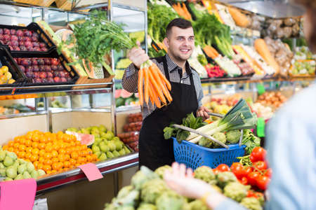Happy seller helping customer to buy vegetables Stock Photo
