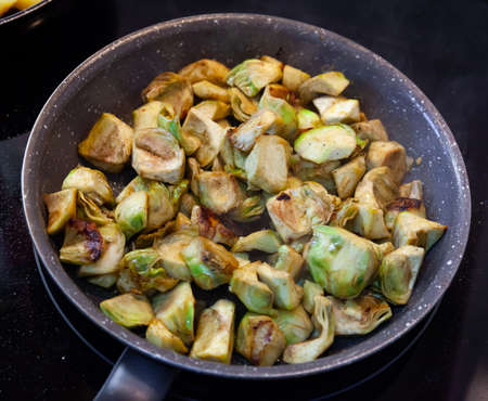 Appetizing artichokes fried in a pan