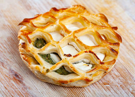 Puff with spinach and goat cheese on wooden surface